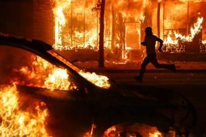 ผู้ประท้วงวิ่งผ่านรถยนต์และอาคารที่กำลังถูกเพลิงเผาผลาญ บริเวณถนนสายหนึ่งเมื่อวันเสาร์ (30 พ.ค.) ในเมืองเซนต์พอล รัฐมินนิโซตา ขณะที่การประท้วงยังดำเนินอย่างต่อเนื่องภายหลังการเสียชีวิตของ จอร์จ ฟลอยด์ ซึ่งตายหลังจากตำรวจที่เข้าจับกุมเขาใช้เข่าหนีบคอเขาเอาไว้เป็นเวลาเกือบ 9 นาทีเมื่อวันที่ 25 พ.ค.