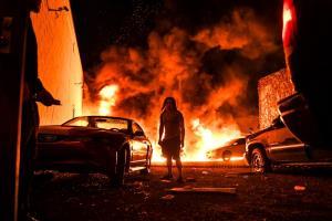 ชายผู้หนึ่งพยายามลากรถยนต์ซึ่งยังไม่เสียหายไปยังพื้นที่ปลอดภัย ขณะที่รถยนต์คันอื่นๆ ถูกไฟเผาผลาญ ณ โรงรถท้องถิ่นแห่งหนึ่งในเมืองมินนิอาโปลิส รัฐมินนิโซตา เมื่อวันที่ 29 พฤษภาคม 2020 ระหว่างการประท้วงการเสียชีวิตของ จอร์จ ฟลอยด์ ซึ่งลุกลามบานปลายกลายเป็นความรุนแรง
