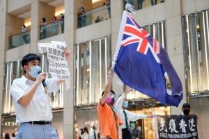 นักเคลื่อนไหวชาวฮ่องกงรายหนึ่งโบกสะบัดธงฮ่องกงในยุคที่เป็นอาณานิคมอังกฤษ ขณะที่อีกคนถือป้ายข้อความวิงวอนให้ทหารสหรัฐฯเข้ามาช่วยเหลือชาวฮ่องกง  เมื่อวันที่ 1 มิ.ย.