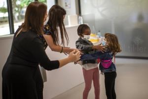 คุณครูพยายามห้ามไม่ให้ เวนดี โอทิน วัย 6 ขวบ กับ อูมู ซาลาม เนียง อายุเท่ากัน สวมกอดกัน ขณะเด็กทั้งสองเจอหน้ากันในวันแรกที่โรงเรียนกลับเปิดขึ้นมาใหม่ภายหลังการล็อกดาวน์อย่างยาวนาน ณ โรงเรียนประถมแห่งหนึ่งในเมืองบาร์เซลโลนา ประเทศสเปน เมื่อวันจันทร์ (8 มิ.ย.)
