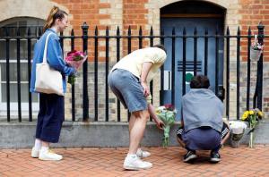 ประชาชนวางช่อดอกไม้ไว้อาลัยเหยื่อ เอาไว้ข้างๆ แนวเส้นกั้นของตำรวจ ณ จุดเกิดเหตุคนร้ายไล่แทงผู้คนในเมืองเรดดิง