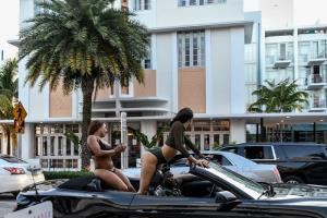สาวๆ ในรถคันหนึ่งขณะขับผ่านหาดไมอามี รัฐฟลอริดา วันศุกร์ (26 มิ.ย.)