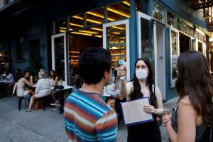 พนักงานร้านอาหารแห่งหนึ่งในย่านแมนฮัตตัน เมืองนิวยอร์ก ประเทศสหรัฐฯ กำลังตรวจวัดอุณหภูมิลูกค้าผู้มาใช้บริการ ส่วนหนึ่งในมากตรการสกัดโควิด-19 เมื่อช่วงสุดสัปดาห์ที่ผ่านมา อย่างไรก็ตามร้านอาหาร บาร์ และชายหาดในอเมริกา ซึ่งเป็นประเทศที่ได้รับผลกระทบจากไวรัสโคโรนาสายพันธุ์ใหม่รุนแรงที่สุดในโลก ถูกสั่งปิดอีกครั้งตั้งแต่แคลิฟอร์เนียไปจนถึงฟลอริดา ขณะที่ยอดผู้ติดเชื้อในหลายรัฐยังพุ่งทะยาน
