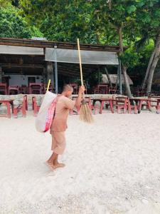 """โซเชียลชื่นชม! """"ลุงอาว"""" ชาวเมียนมา เดินเก็บขยะหน้าหาดทรายแดง เกาะเต่า"""
