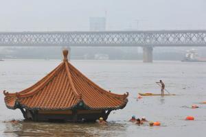 เก๋งจีนชมวิวแม่น้ำในเมืองหนันชาง นครอู่ฮั่น ถูกน้ำท่วมเห็นแต่หลังคา ระดับน้ำในแยงซีเกียงช่วงเมืองอู่ฮั่น สูงถึง 28.52 เมตรซึ่งเกินขีดเตือนภัยไป 1.03 เมตร ภาพถ่ายเมื่อวันที่ 8 ก.ค. 2020 (แฟ้มภาพรอยเตอร์ส)