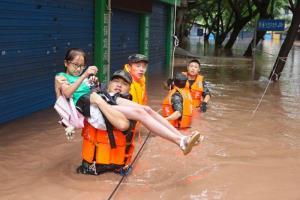 เจ้าหน้าจากหน่วยตำรวจกึ่งทหารกำลังช่วยอพยพชาวบ้านหนีภัยน้ำท่วมในวั่นโจว นครฉงชิ่ง ภาพ 16 ก.ค. 2020 (ภาพ รอยเตอร์ส)