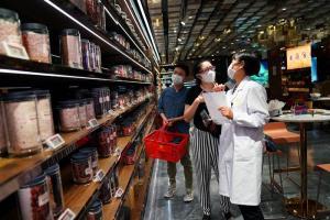 ลูกค้าในร้านยาแผนจีนกำลังเลือกซื้อยาจีนในร้านสาขาของยักษ์ใหญ่ยาจีนถงเหรินถังในกรุงปักกิ่ง ขณะที่โควิด-19 ยังระบาดในจีน ภาพ 29 ก.ค.2020 (ภาพ รอยเตอร์ส)