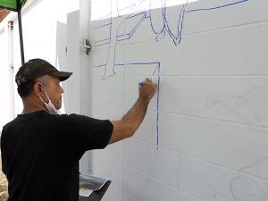 พินิจอาสาทำความดี-ศิลปินร่วมวาดภาพพื้นกำแพงทางเข้า-ออกถนนเลียบแม่น้ำปัตตานี