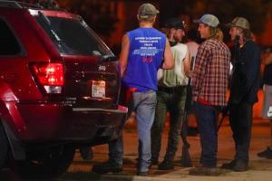 กลุ่มชายผิวขาวถือปืนไรเฟิล ซึ่งเรียกตัวเองเป็นหน่วยกำลังอาวุธพิทักษ์ท้องถิ่น ยืนดูพวกผู้ประท้วงบนถนนในเมืองเคโนชา รัฐวิสคอนซิน เมื่อคืนวันอังคาร (25 ส.ค.) ซึ่งเป็นคืนที่เกิดการปะทะกันระหว่างพวกผู้ประท้วงกับเด็กหนุ่มผิวขาวคนหนึ่งที่เป็นสมาชิกของกลุ่มเช่นนี้  โดยในที่สุดเด็กหนุ่มคนนี้ยิงคนตายไป 2 บาดเจ็บอีก 1