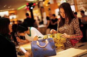 สาวจีนกำลังเลือกซื้อกระเป๋าแบรนด์เนม (แฟ้มภาพ รอยเตอร์ส)