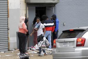 มีคนหิ้วข้าวของ เดินออกมาจากร้านค้าที่ได้รับความเสียหายระหว่างการประท้วงที่เมืองฟิลาเดลเฟีย เมื่อวันอังคาร (27 ต.ค.)