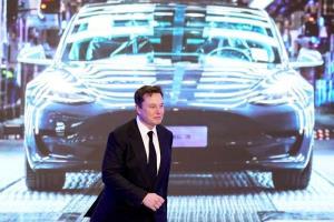อีลอน มัสก์ ซีอีโอ Tesla Inc กำลังเดินผ่านหน้าจอแสดงภาพ Tesla Model 3 ระหว่างวงพิธีเปิดตัวโครงการผลิตรถ รุ่น Model Y ที่โรงงานเทสลาในเซี่ยงไฮ้ ภาพวันที่ 7 ม.ค. 2020 (แฟ้มภาพรอยเตอร์ส)