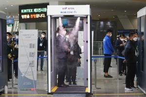 ผู้เข้าร่วมงานยืนอยู่ในห้องปล่อยสารฆ่าเชื้อ ซึ่งเป็นหนึ่งในมาตรการป้องกันไวรัสโคโรนาสายพันธุ์ใหม่ สำหรับผู้ที่ต้องการเข้าไปชมงานนิทรรศการสินค้าทางการทหาร DX Korea 2020 ซึ่งจัดที่เมืองโกยาง เกาหลีใต้ ในวันพุธ (18 พ.ย.)