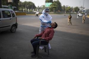 บุคลากรสาธารณสุขเก็บตัวอย่างจากชายผู้หนึ่งเพื่อนำมาตรวจเชื้อโรคโควิด-19 ระหว่างการสุ่มตรวจประชาชนในบริเวณพื้นที่ชานเมืองของกรุงนิวเดลี ประเทศอินเดีย เมื่อวันพุธ (18 พ.ย.)
