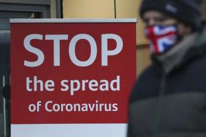 ชายสวมหน้ากากป้องกันใบหน้าซึ่งทำเป็นธงยูเนียนแจ็กของสหราชอาณาจักร เดินผ่านแผ่นป้ายเตือนภัยไวรัสโคโรนา บริเวณด้านนอกธนาคารแห่งหนึ่งในเมืองกลาสโกว์ ของสกอตแลนด์ ตอนเช้าวันอังคาร (5 ม.ค.) โดยที่ทั่วทั้งสกอตแลนด์ก็เริ่มใช้มาตรการล็อกดาวน์ที่เข้มงวดยิ่งขึ้น
