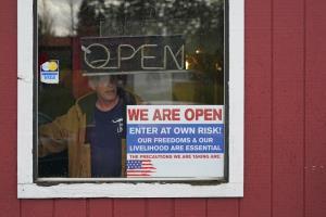 ภาพถ่ายไว้เมื่อ 4 มกราคม แสดงให้เห็นหน้าต่างของร้านอาหาร ฟาร์ม บอย ไดรฟ์อิน ใกล้ๆ เมืองโอลิมเปีย รัฐวอชิงตัน  ติดป้ายเขียนว่า ร้านเปิดอยู่ ให้เสี่ยงเอาเองว่าจะเข้าหรือไม่  ทั้งนี้ทางการหลายท้องถิ่นซึ่งโควิด-19 ระบาดหนัก ได้ออกมาตรการห้ามรับประทานอาหารภายในร้าน แต่เวลานี้มีร้านจำนวนมากขึ้นทั่วสหรัฐฯพากันท้าทายคำสั่งเช่นนี้ แม้อาจจะถูกปรับหรือถูกลงโทษอย่างอื่นๆ โดยให้เหตุผลว่าแบกรับการขาดรายได้นานๆ ไม่ไหวแล้ว