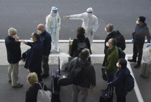 เจ้าหน้าที่ในชุดป้องกันการติดเชื้อ นำทางสมาชิกคณะผู้เชี่ยวชาญนานาชาติขององค์การอนามัยโลก ขณะเดินทางมาถึงสนามบินในเมืองอู่ฮั่น มณฑลหูเป่ย ทาภาคกลางของจีน เมื่อวันพฤหัสบดี (14 ม.ค.)