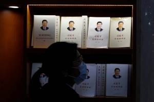 """หญิงจีนเดินผ่านหน้าชั้นวางหนังสือ """"สี จิ้นผิง: ธรรมาภิบาลจีน""""  และฉบับแปลเวอร์ชั่นภาษาต่างๆ ที่ร้านหนังสือ ภาพวันที่ 1 มี.ค.2021 (ภาพรอยเตอร์ส)"""