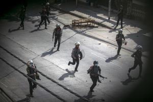 ตำรวจซึ่งบางคนถือปืน วิ่งไล่พวกผู้ประท้วงในย่างกุ้ง วันพุธ (3 มี.ค.)