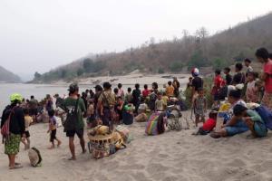 ผู้ลี้ภัยชาวกะเหรี่ยงจำนวนมากยืนอยู่ริมฝั่งแม่น้ำสาละวินหลังหลบหนีความรุนแรงในพื้นที่. --  Reuters.