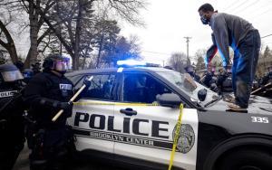 ชายผู้หนึ่งยืนอยู่บนรถตำรวจหลังจากโยนก้อนอิฐใส่กระจกด้านหน้าของรถ บริเวณใกล้ๆ จุดเกิดเหตุที่ตำรวจถูกกล่าวหาว่ายิงหนุ่มผิวดำเสียชีวิตในเมืองบรูกลิน เซ็นเตอร์ วันอาทิตย์ (11 เม.ย.)