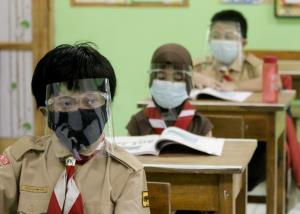 นักเรียนชั้นประถมของโรงเรียนแห่งหนึ่งในกรุงจาการ์ตาต้องสวมทั้งหน้ากากอนามัยและเฟซชิลด์เข้าชั้นเรียน ท่ามกลางสถานการณ์การระบาดของโควิด-19