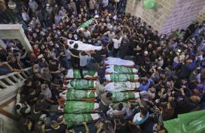 ชาวปาเลสไตน์ชุมนุมกันเพื่อละหมาดให้ผู้เสียชีวิต รอบๆ ศพของนักรบฮามาส 13 คน ซึ่งถูกสังหารจากการโจมตีทางอากาศของอิสราเอล ณ พิธีศพซึ่งจัดขึ้นที่มัสยิดอัล-โอมารี ในเมืองกาซาซิตี้ วันพฤหัสบดี (13 พ.ค.)