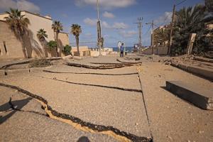 หนุ่มน้อยปาเลสไตน์เดินไปตามถนนสายหลักนำไปสู่ทะเลในเมืองกาซาซิตี้ ซึ่งอยู่ในสภาพเสียหายยับเยิน ภายหลังถูกอิสราเอลโจมตีทิ้งระเบิดทางอากาศอย่างหนักหน่วงในวันจันทร์ (17 พ.ค.)