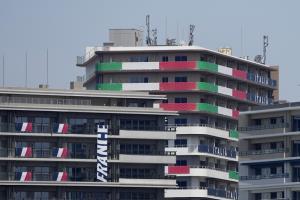 ธงชาติและป้ายชื่อประเทศแขวนอยู่ที่อพาร์ตเมนต์ของนักกีฬาทีมชาติฝรั่งเศส และทีมชาติอิตาลี ในหมู่บ้านนักกีฬาโตเกียวโอลิมปิก เมื่อวันจันทร์ (19 ก.ค.) ขณะนักกีฬาชาติต่างๆ ทยอยเดินทางมาถึง