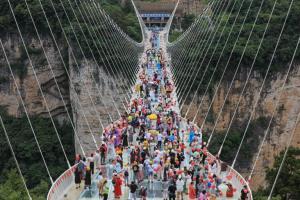 กลุ่มนักท่องเที่ยวกำลังชมวิวบนสะพานกระจกในแหล่งท่องเที่ยวชื่อก้องโลก จางจยาเจี้ย มณฑลหูหนัน ภาพเมื่อวันที่ 20 มิ.ย.2021  (แฟ้มภาพ เอเอฟพี)