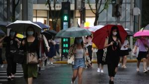 ผู้อยู่อาศัยใช้ร่มข้ามสี่แยกในเซี่ยงไฮ้ ประเทศจีน เมื่อวันอังคารที่ 14 กันยายน 2021  หลังจากไต้ฝุ่นจันทูเคลื่อนตัวขึ้นฝั่งเมื่อวันจันทร์ ทำให้เกิดฝนตกหนักและลมกระโชกแรง  (เครดิตภาพ AP /เฉินซี)